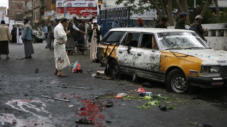 People gather at the site of a suicide bombing in Sanaa, Yemen, Thursday, Oct. 9, 2014. A suicide bomber struck at the center of the Yemeni capital of Sanaa on Thursday, setting off his explosives at a gathering of supporters of the rebel Shiite Houthis who recently overran the city, security officials said. (AP Photo)