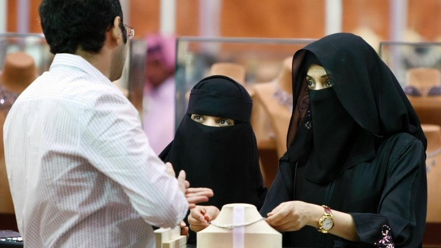 FILE - In this Saturday, March 21, 2009 file photo, Saudi women look at jewelry at a gold fair in Riyadh, Saudi Arabia. Human rights group Amnesty International says Saudi authorities have used an iron grip to consolidate power and unleashed a ruthless campaign of persecution against peaceful activists to silence criticism of the state. (AP Photo/Hassan Ammar, File)