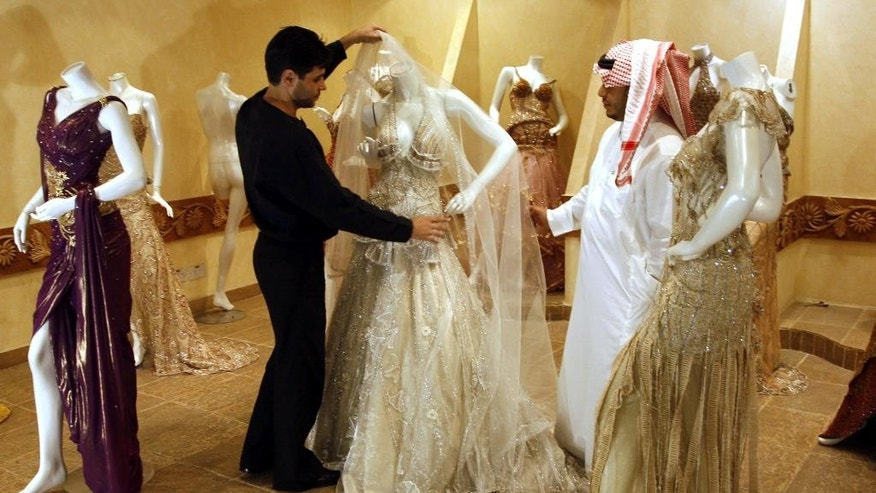 FILE - In this Sunday, Aug. 3, 2008 file photo, a Saudi man, right, buys a wedding dress at a shop in Riyadh, Saudi Arabia. Human rights group Amnesty International says Saudi authorities have used an iron grip to consolidate power and unleashed a ruthless campaign of persecution against peaceful activists to silence criticism of the state. (AP Photo, File)