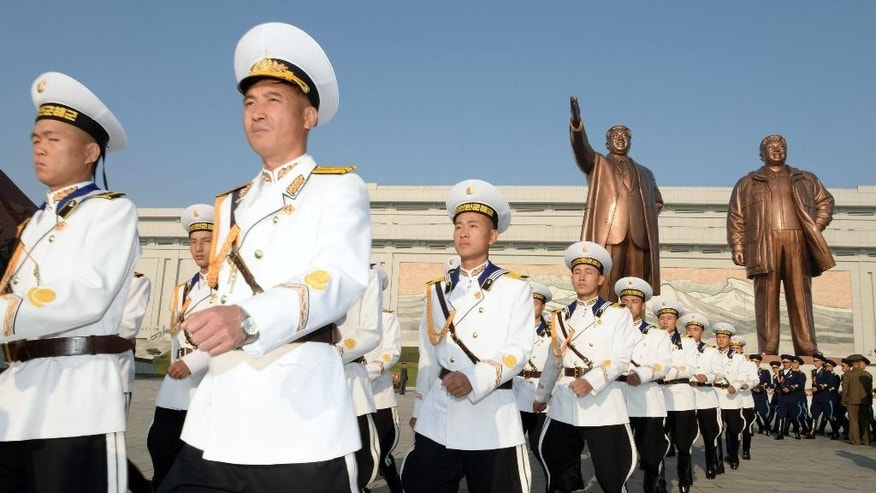 North Korean military personnel march as they visit the statues of late leaders, Kim Il Sung, left, and Kim Jong Il on Mansudae to mark the 69th anniversary of the founding of the ruling Workers' Party of Korea, in Pyongyang, North Korea Friday, Oct. 10, 2014. (AP Photo/Kyodo News) JAPAN OUT, MANDATORY CREDIT