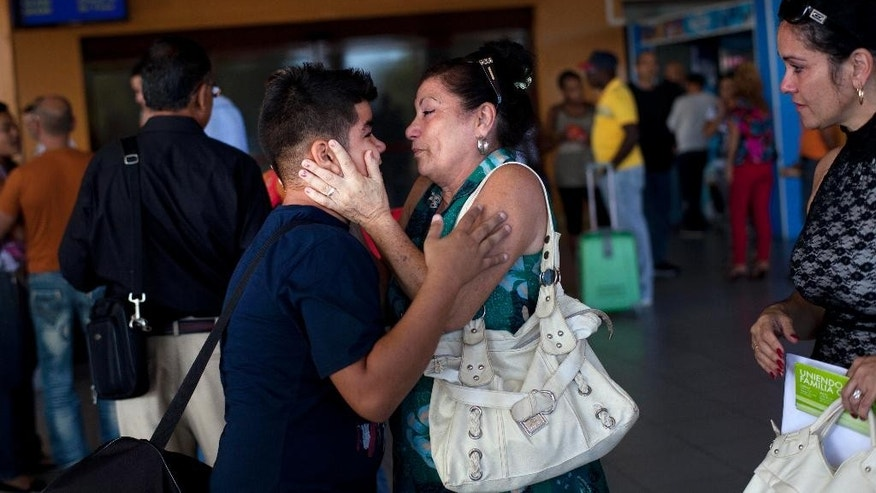 FILE - In this Jan. 14, 2013 file photo, Ivan Lee, 12, says goodbye to a family member before traveling to Miami, Florida, where he will reunite with his mother who has been living there for years, as he prepares to board a plane at airport after a new law took effect ending the island's much-hated exit visa requirement, in Havana, Cuba. The government extended in 2013 the length of time Cubans can be gone without losing residency rights from one year to two. That means migrants now can obtain U.S. residency and still return to Cuba for extended periods, receive government benefits and even invest money earned in the U.S. (AP Photo/Ramon Espinosa, File)