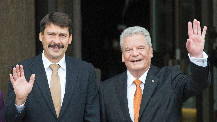 German President Joachim Gauck, right, waves besides his Hungarian counterpart Janos Ader,  left, before the beginning of the ceremonial act at the 25th anniversary of the peaceful revolution in Leipzig, Germany, Thursday, Oct. 9, 2014. The city commemorates the autumn of 1989 when the so-called Monday demonstrations ushered in the Fall of the Berlin Wall. On Oct. 9, 1989, the major decisive demonstrations took place against the former regime of the GDR – 70,000 people paved the way for changes. (AP Photo/Jens Meyer)