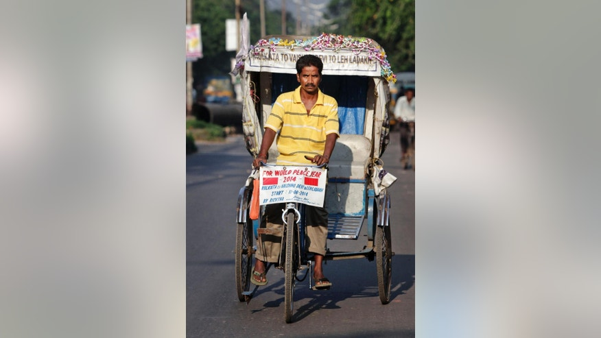 Satyen Das rides his rickshaw on a road in Kolkata, India, Thursday, Oct. 9, 2014. It took 68 days for Das to laboriously pedal his rickety, self-remodeled bicycle rickshaw from the seaside Indian city of Kolkata to the roof of the world - a 5,369-meter (17,600-foot) Himalayan pass. His goal: to promote his chassis as an environmentally sound travel option. (AP Photo/Bikas Das)