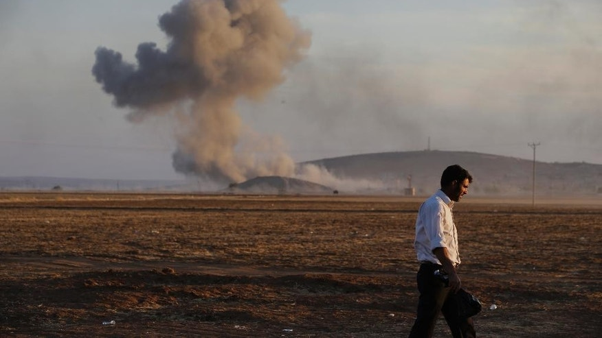 A Turkish Kurd walks away as airstrikes hit Kobani, inside Syria, as fighting intensifies between Syrian Kurds and the militants of Islamic State group, in Mursitpinar, on the outskirts of Suruc, at the Turkey-Syria border, Wednesday, Oct. 8, 2014. Kobani, also known as Ayn Arab and its surrounding areas have been under attack since mid-September, with militants capturing dozens of nearby Kurdish villages. (AP Photo/Lefteris Pitarakis)