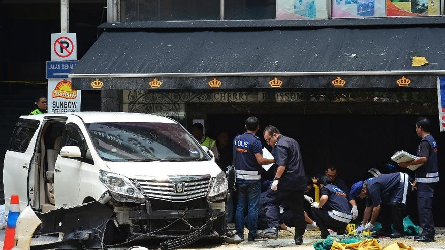 Malaysian forensic police officers investigate the scene where a grenade exploded outside a night club in Kuala Lumpur, Malaysia, Thursday, Oct. 9, 2014. Malaysian police say one person died and 13 others injured when a hand grenade blew up Thursday at the popular tourist belt in the country's largest city. (AP Photo) MALAYSIA OUT