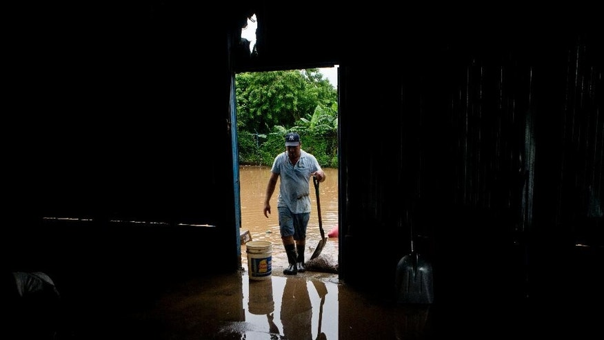 A worker is a reflected in a pudle water while cleaning a rice warehouse flooded after the Ochomogo river burst its banks in Rivas, Nicaragua, Thursday, Oct 9, 2014. The country's Institute of Territorial Studies reports that 14.9 inches (378 millimeters) of rain fell in just 24 hours, the most on record. The record rains unleashed landslides and flooding that swamped hundreds of homes. (AP Photo/Esteban Felix)