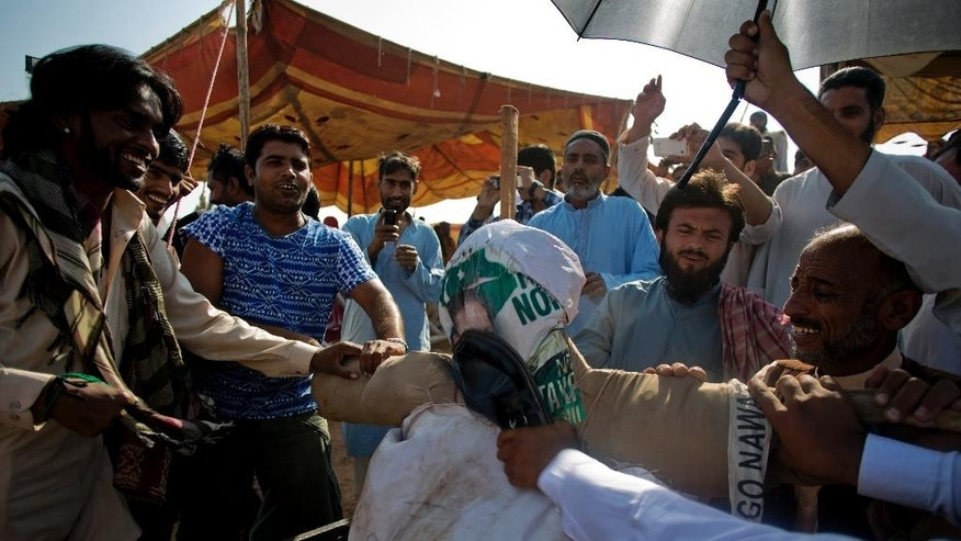 Supporters of Pakistan's cricketer-turned politician, Imran Khan, beat an effigy of Pakistani prime minister Nawaz sharif during a sit-in protest outside a parliament building in Islamabad, Pakistan, Monday, Oct. 6, 2014. Anti-government protesters led by opposition leaders Khan and Muslim cleric Tahir-ul-Qadri converged on the capital in mid-August, demanding Sharif's ouster over alleged fraud in last year's election. (AP Photo/B.K. Bangash)