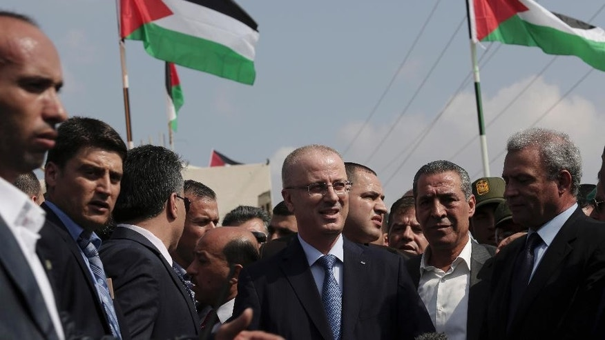 Palestinian Prime Minister Rami Hamdallah, center, arrives at the Palestinian side of the Beit Hanoun border crossing in the northern Gaza Strip, Thursday, Oct. 9, 2014. Members of the new Palestinian unity government assembled in Gaza on Thursday for their first Cabinet session in the war-battered territory - a largely symbolic meeting meant to mark the end of absolute Hamas control of the coastal strip. (AP Photo/Adel Hana)