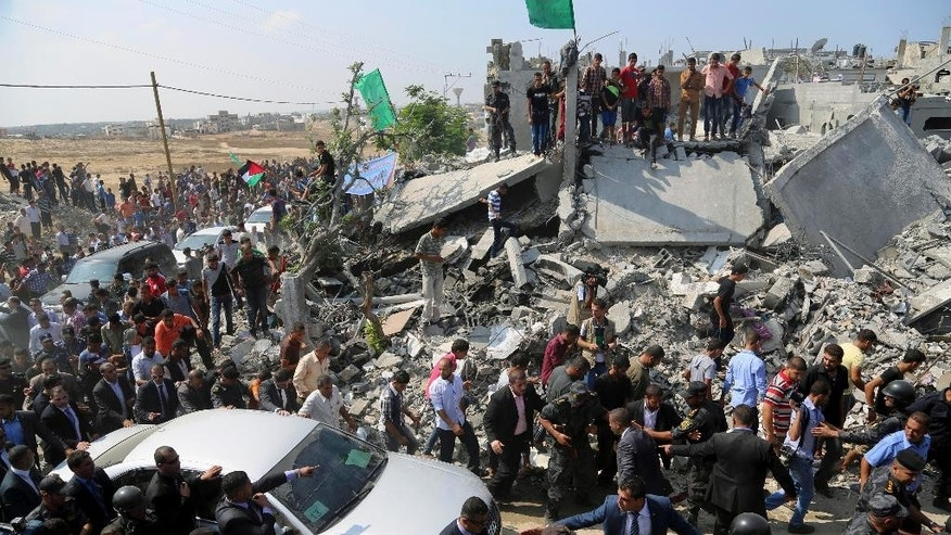 Members of the Palestinian security gather around the car carrying Prime Minister Rami Hamdallah on a tour to destroyed houses in an area east of the Beit Hanoun border crossing in the northern Gaza Strip, Thursday, Oct. 9, 2014. Members of the new Palestinian unity government assembled in Gaza on Thursday for their first Cabinet session in the war-battered territory - a largely symbolic meeting meant to mark the end of absolute Hamas control of the coastal strip. (AP Photo/Adel Hana)