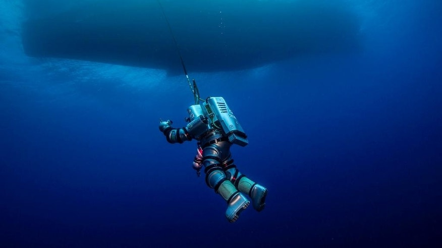 In this undated photo provided by Argo via the Greek Culture Ministry on Thursday, Oct. 9, 2014, a diver wearing a new metal suit that allows humans to reach great depths without decompressing, descends over the Antikythera wreck off the island of Antikythera in southern Greece. The ministry said Thursday that a three-week underwater project to revisit the Roman-era wreck, first investigated more than a century ago, has completed detailed maps of the seabed and pinpointed potential metal artifacts. Divers have recovered a bronze spear that was probably part of a large statue, metal fittings from the ship and a vase. (AP Photo/ARGO via Greek Culture Ministry, Brett Seymour)