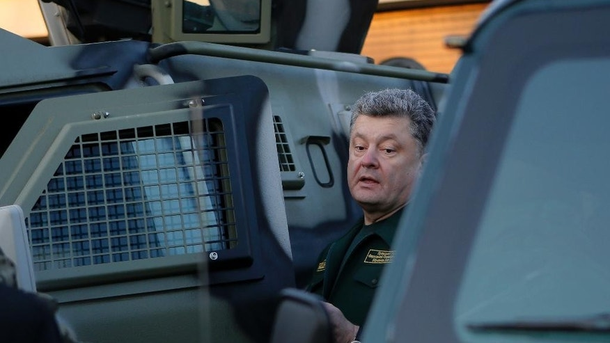 Ukrainian President Petro Poroshenko inspects military armored personnel carriers during his visit in a State Border Guard Service  in Kiev, Ukraine, Tuesday, Oct. 7, 2014. (AP Photo/Sergei Chuzavkov)