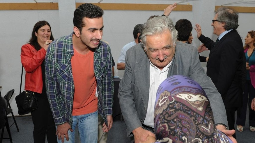 In this picture released by Uruguay's presidential press office, Uruguay's President Jose Mujica, right, welcomes a Syrian woman who arrived with a group of refugees to the Catholic Marista Brothers of San Jose home where they will reside temporarily, on the outskirts of Montevideo, Uruguay, Thursday, Oct. 9, 2014. Uruguay's government has received the first group of Syrian refugees to arrive in the South American country. The 42 refugees seeking shelter from the civil war were taken to a new home on the city's outskirts. The government has agreed to receive a total of 120 Syrian refugees, being the first one in the region to assume all resettlement costs.  (AP Photo/Uruguay Presidential Press Office)