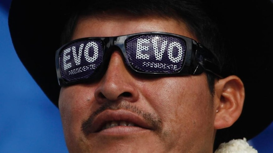 A supporter of Bolivia's President Evo Morales, who is running for re-election with the Movement Toward Socialism, MAS, attends the closing campaign rally in El Alto, Bolivia, Wednesday, Oct. 8, 2014. Bolivia will hold general elections on Sunday. (AP Photo/Juan Karita)