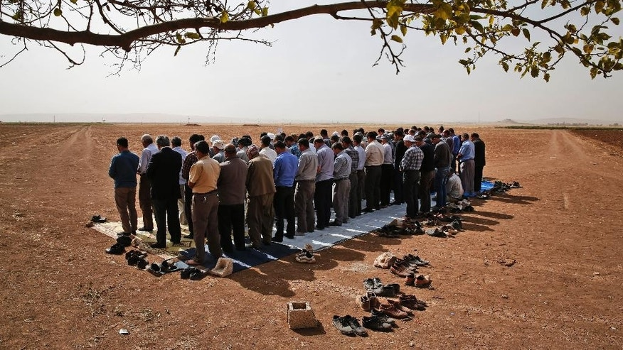 Turkish Kurds in the outskirts of Suruc, on the Turkey-Syria border, offer their Friday prayers as they gather to support Syrian Kurds over the border in nearby Kobani, Syria, where fighting between Syrian Kurds and the militants of Islamic State group intensified, Friday, Oct. 10, 2014.  Kobani, also known as Ayn Arab, and its surrounding areas, has been under assault by extremists of the Islamic State group since mid-September and is being defended by Kurdish fighters. (AP Photo/Lefteris Pitarakis)