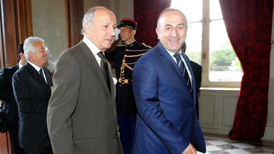 French Foreign Affairs Minister Laurent Fabius, left, welcomes his Turkish  counterpart Mevlut Cavusoglu prior to their talks in Paris, Friday Oct. 10 , 2014.  The Islamic State group is fighting for control of the embattled town of Kobani in Syria, on the border with Turkey  (AP Photo/Jacques Brinon)