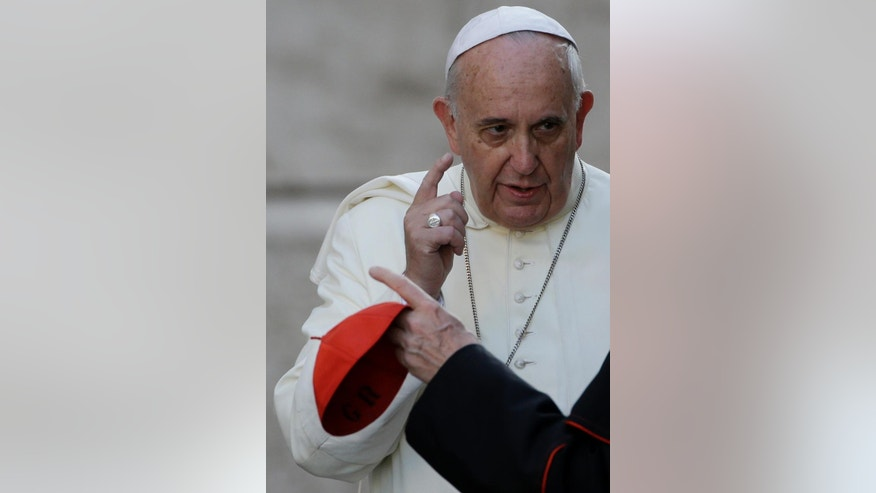 Pope Francis gestures as he talks with Cardinal Gianfranco Ravasi as he  arrives for an afternoon session of a two-week synod on family issues at the Vatican, Thursday, Oct. 9, 2014. (AP Photo/Gregorio Borgia)