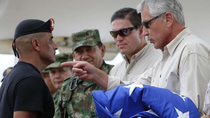 U.S. Defense Secretary Chuck Hagel, right, talks to an army soldier as Colombia's Defense Minister Juan Carlos Pinzon, second right, watches, at the Tolemaida military base, in Melgar, Colombia, Friday, Oct. 10, 2014. Hagel is on a six-day, three-country trip to South America. Hagel will also travel to Chile and Peru, where he will attend a conference of defense ministers from the Americas. (AP Photo/Fernando Vergara)