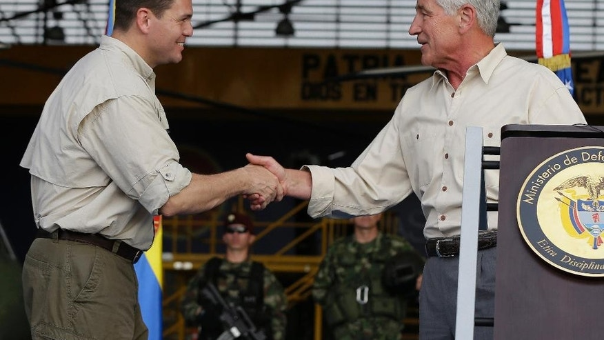U.S. Defense Secretary Chuck Hagel, right, shakes hands with Colombia's Defense Minister Juan Carlos Pinzon, after a press conference at the Tolemaida military base, in Melgar, Colombia, Friday, Oct. 10, 2014. Hagel is on a six-day, three-country trip to South America. Hagel will also travel to Chile and Peru, where he will attend a conference of defense ministers from the Americas. (AP Photo/Fernando Vergara)