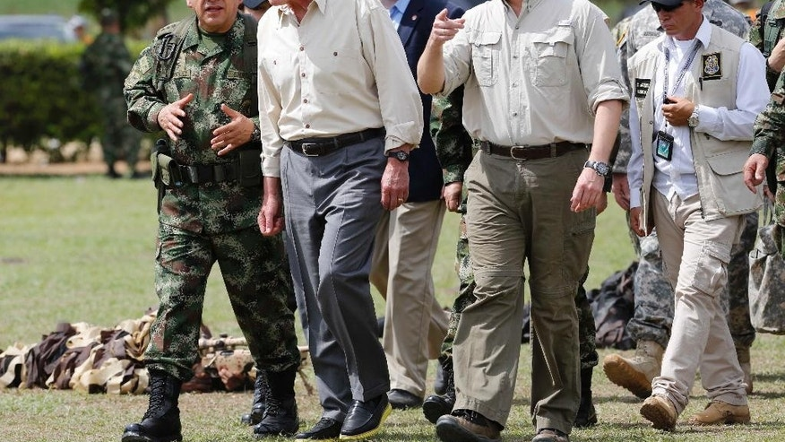 Colombian Armed Forces Commander, Gen. Juan Pablo Rodriguez, left, and Defense Minister Juan Carlos Pinzon, right, lead a tour for U.S. Defense Secretary Chuck Hagel, center, at the Tolemaida military base, in Melgar, Colombia, Friday, Oct. 10, 2014. Hagel is on a six-day, three-country trip to South America. Hagel will also travel to Chile and Peru, where he will attend a conference of defense ministers from the Americas. (AP Photo/Fernando Vergara)