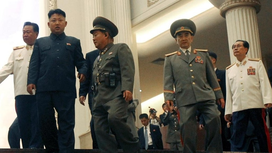 FILE - In this July 27, 2013 file photo, North Korean leader Kim Jong Un, second left, tours the newly opened Fatherland Liberation War Museum, accompanied by Yang Hyong Sop, second right, vice president of the Presidium of North Korea's parliament, his late uncle Jang Song Thaek, right, and Vice Marshal Choe Ryong Hae, left, as part of celebrations for the 60th anniversary of the Korean War armistice in Pyongyang, North Korea. North and South Korea traded machine-gun and rifle fire Friday, Oct. 10, 2014 after South Korean activists released anti-Pyongyang propaganda balloons across the border, officials said. The exchange of fire comes as speculation grows about the condition of the North Korea's authoritarian leader who has been out of public view for more than a month. He missed a major anniversary event on Friday for the first time in three years. (AP Photo/Wong Maye-E, File)