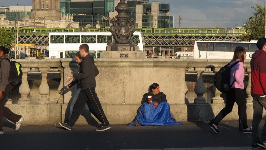 In this picture taken on Monday, Oct. 6, 2014, pedestrians pass a street beggar on O'Connell Bridge in central Dublin, Ireland, with the city's financial district in the background. Ireland is rebounding strongly from its 2010 international bailout and seeking to repay its International Monetary Fund loans early to save on interest costs. (AP Photo/Shawn Pogatchnik)