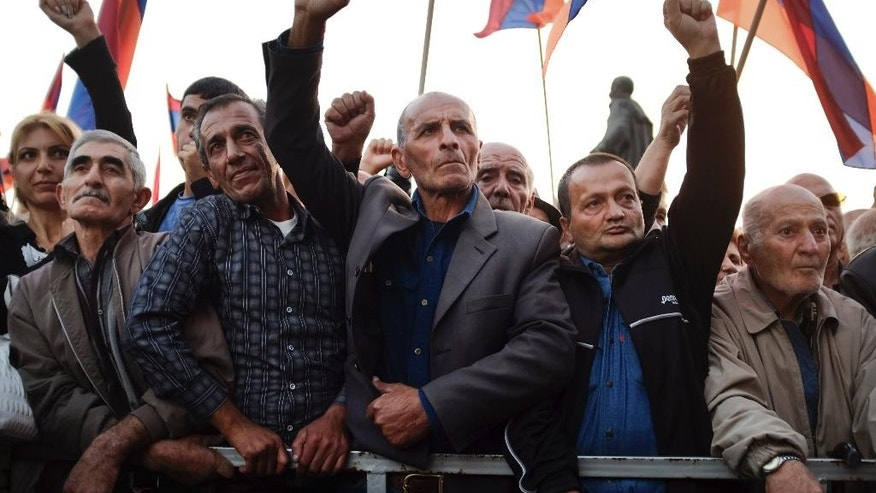 Protesters hold Armenian flags during an opposition rally in Yerevan, Armenia, Friday, Oct. 10, 2014. About 12,000 people rallied in the capital of Armenia to protest an impending constitutional reform that they fear could be abused by the incumbent president. (AP Photo/Vahan Stepanyan, PAN Photo)