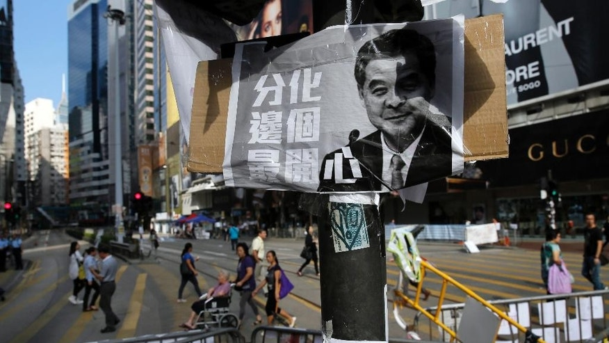 "A picture of Chief Executive Leung Chun-ying is hanged on a pole next to some barricades on a main road in the occupied areas at Causeway Bay district in Hong Kong, Friday, Oct. 10, 2014. A pro-democracy protest that has blocked main roads in Hong Kong for almost two weeks could drag on for days yet, after talks aimed at resolving a bitter standoff between the city's government and student demonstrators collapsed Thursday. The Chinese words read: ""When divided up, see who will be most happy."" (AP Photo/Vincent Yu)"