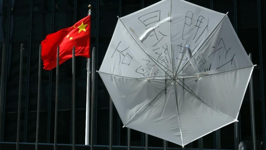 "An umbrella is displayed on a fence next to a Chinese flag at the government headquarters in Hong Kong's Admiralty, Friday, Oct. 10, 2014. A pro-democracy protest that has blocked main roads in Hong Kong for almost two weeks could drag on for days yet, after talks aimed at resolving a bitter standoff between the city's government and student demonstrators collapsed Thursday. The slogan on the umbrella reads: ""Are you isolated from the world?"" (AP Photo/Kin Cheung)"