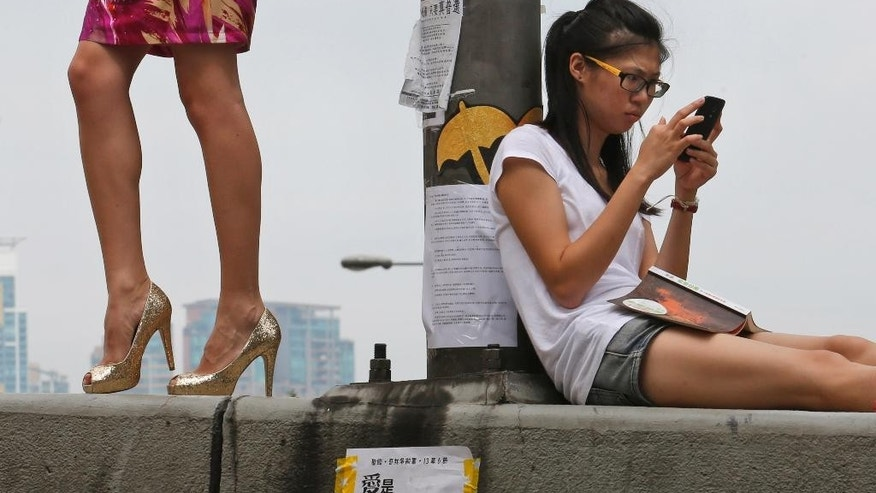 A model, left, poses for a fashion photo shooting as a protester sits on a main road in the occupied areas outside government headquarters in Hong Kong's Admiralty, Friday, Oct. 10, 2014. A pro-democracy protest that has blocked main roads in Hong Kong for almost two weeks could drag on for days yet, after talks aimed at resolving a bitter standoff between the city's government and student demonstrators collapsed Thursday. (AP Photo/Kin Cheung)