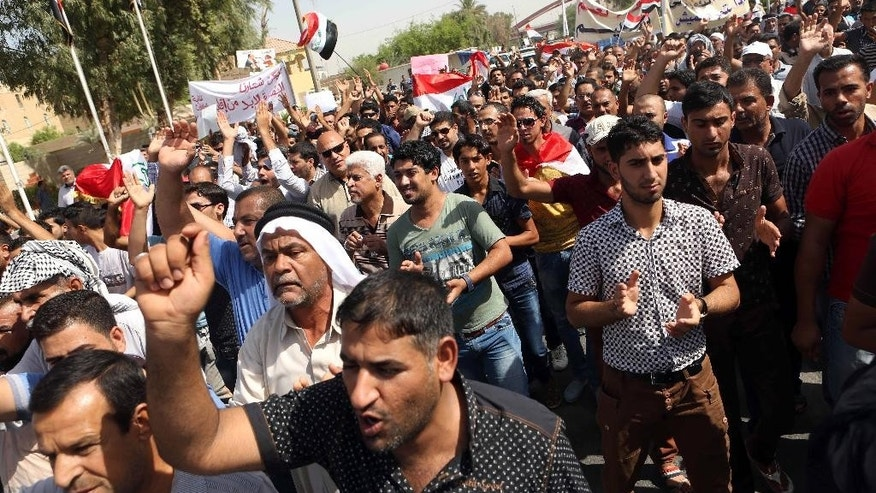 In this  Saturday, Sept. 27, 2014 photo, Basra residents chant slogans supporting the creation of Basra region, in front of the Basra provincial headquarters during a demonstration in Basra, 340 miles (550 kilometers) southeast of Baghdad, Iraq.  Haider al-Abadi, named Iraq's prime minister on Sept. 8, has made decentralization a paramount theme in his platform as the new head of government, with a plan to give greater autonomy to provincial governments and construct a national guard in which recruits and leadership are conscripted from local populations.  (AP Photo/Nabil al-Jurani)
