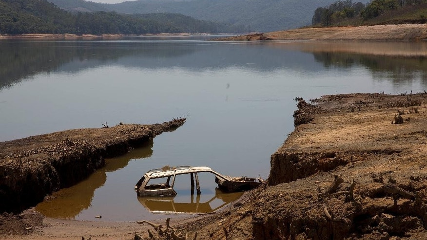 A car is revealed by the receding water in the Atibainha dam, part of the Cantareira System that provides water to the Sao Paulo metropolitan area, in Nazare Paulista, Brazil, Friday, Oct. 10, 2014. The dam is drying up due to the worst drought to hit Sao Paulo in 84 years. (AP Photo/Andre Penner)