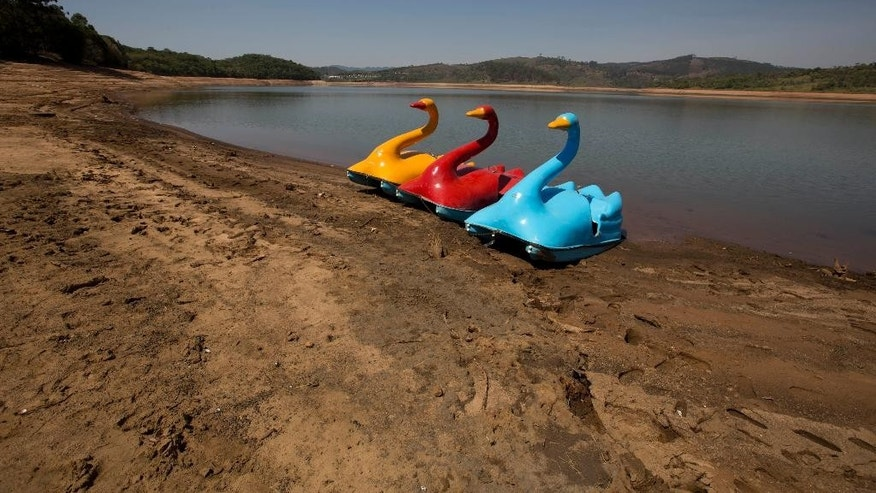 Pedal boats stand on the receding banks of the Atibainha dam, part of the Cantareira System responsible for providing water to the Sao Paulo metropolitan area, in Nazare Paulista, Brazil, Friday, Oct. 10, 2014. The region got only a third of the usual rain during Brazil's wet season from December to February.  (AP Photo/Andre Penner)
