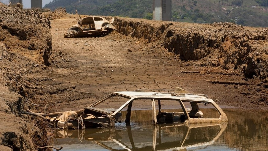 The frames of cars are revealed by the receding water line in the Atibainha dam, part of the Cantareira System that provides water to the Sao Paulo metropolitan area, in Nazare Paulista, Brazil, Friday, Oct. 10, 2014. Due to the worst drought in 84 years, the Basic Sanitation Company of the State of Sao Paulo has offered discounts to consumers who reduce monthly consumption by 20 percent, among other measures. (AP Photo/Andre Penner)