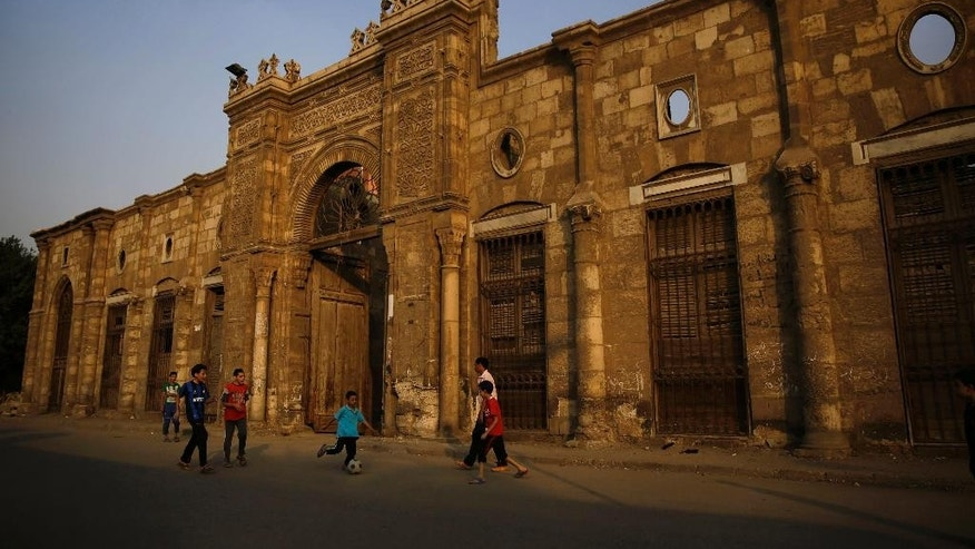 Children play soccer in front of an old building in the vast necropolis known as the City of the Dead in Cairo, Egypt, Friday, Oct. 10, 2014. The structure was originally built as a palace in Cairo's Garden City neighborhood in the 1820s. Its facade was moved to the current location in the early 1900s, remodeled as a home and served until it was abandoned. (AP Photo/Hassan Ammar)