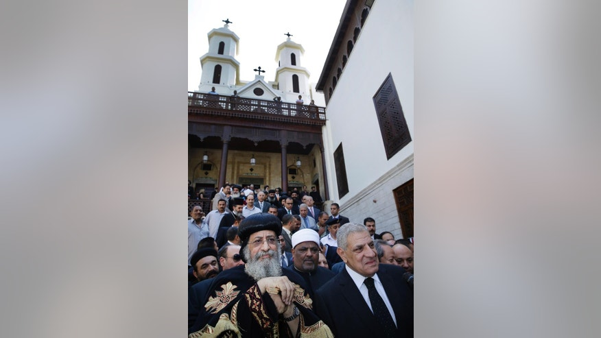 Pope Tawadros II, the Patriarch of the Coptic Orthodox Church, left, and Prime Minister Ibrahim Mehleb, right, attend a ceremony marking the end of a $5.4 million restoration project of the Hanging Church in Cairo, Egypt, Saturday, Oct. 11, 2014. Egyptian officials are celebrating the completion of a 16-year old restoration project of Saint Virgin Mary's Coptic Church, also known as the Hanging Church, one of the oldest in the country that owes the nickname to the fact that it rests above a gatehouse of a 2nd century Roman fortress. The church lies in a complex housing one of the oldest synagogues and the first mosque built in Cairo. (AP Photo/Hassan Ammar)