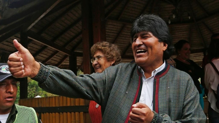 Bolivia's President Evo Morales gives a thumbs up to people at a trout farm where he stopped to eat in Paracti, Bolivia, Saturday, Oct. 11, 2014. Morales stopped here to eat as he traveled to the city where he'll vote in tomorrow's general election. Morales is running for a third term in Sunday's presidential elections. (AP Photo/Juan Karita)