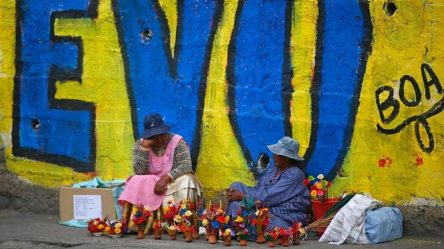 Women sell flowers next to a pro-Evo Morales mural in La Paz, Bolivia, Saturday, Oct. 11, 2014. Former coca growers' union leader Evo Morales seems certain to win an unprecedented third term in Sunday's presidential elections. (AP Photo/Enric Marti)