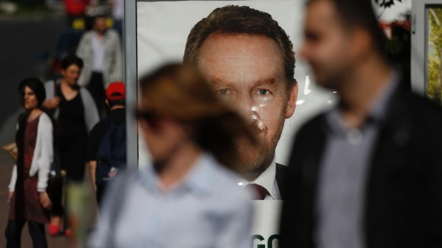 Bosnian people walk near an election poster of Bakir Izetbegovic, leader of the SDA ( Party of Democratic Action) the ruling Bosnian Muslim Party in Bosnia, in Sarajevo, on Thursday, Oct. 9, 2014. Bosnia will hold general elections on Sunday. (AP Photo/Amel Emric)