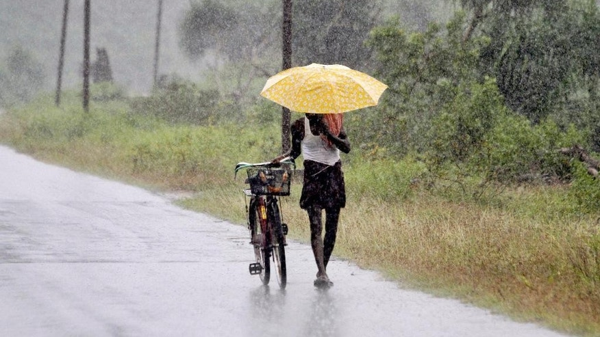 "An Indian man holds an umbrella to protect himself from the heavy rains near Gopalpur, in Ganjam district, 140 kilometers (87 miles) south of Bhubaneswar, India, Saturday, Oct. 11, 2014. The India Meteorological Department described Cyclone Hudhud as a ""very severe"" storm that could pack winds of 195 kilometers (120 miles) per hour and cause torrential rains when it makes landfall near the port city of Visakhapatnam around noon Sunday. (AP Photo/Biswaranjan Rout)"