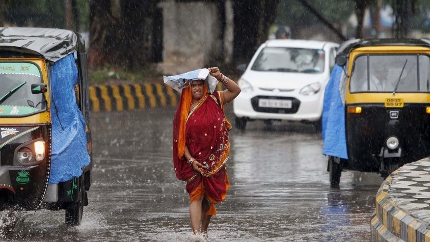 "An Indian woman shields herself with a plastic bag as she walks on a road in the rain, in Bhubaneswar, India, Friday, Oct. 10, 2014. According to Indian Meteorological Department reports, severe cyclonic storm ""Hudhud"" is likely to hit Andhra Pradesh and Orissa coasts Sunday. (AP Photo/Biswaranjan Rout)"