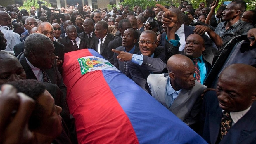 "Friends and family of Haiti's late Dictator Jean-Claude ""Baby Doc"" Duvalier carry his flag draped coffin back to the funeral home after his funeral ceremony in Port-au-Prince, Haiti, Saturday, Oct. 11, 2014. Many had wondered whether the self-proclaimed ""president for life"" would receive a state funeral following his death last Saturday from a heart attack at age 63, but Duvalier's attorney announced late this week that friends and family would arrange a simple and private funeral. (AP Photo/Dieu Nalio Chery)"