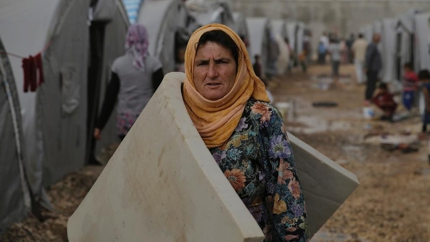 A Syrian Kurdish refugee who fled Kobani, carries a mattress to the family tent at a refugee camp in Suruc, on the Turkey-Syria border, Saturday, Oct. 11, 2014. Kobani, also known as Ayn Arab, and its surrounding areas, has been under assault by extremists of the Islamic State group since mid-September and is being defended by Kurdish  fighters. The onslaught has forced more than 200,000 people to flee across the border into Turkey.(AP Photo/Lefteris Pitarakis)