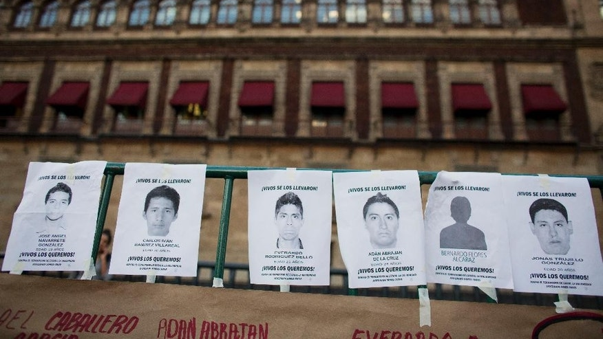 """Flyers printed with the faces of some of the 43 missing students and reading """"You took them alive. We want them back alive,"""" hang on a fence in front of the National Palace, as thousands marched to demand the government find the students who disappeared in southern Guerrero State, in Mexico City, Wednesday, Oct. 8, 2014. Investigators still had no word on whether the 28 bodies found in a mass grave over the weekend included any of the missing students, who disappeared after two attacks allegedly involving Iguala police in which six people were killed and at least 25 wounded. (AP Photo/Rebecca Blackwell)"""