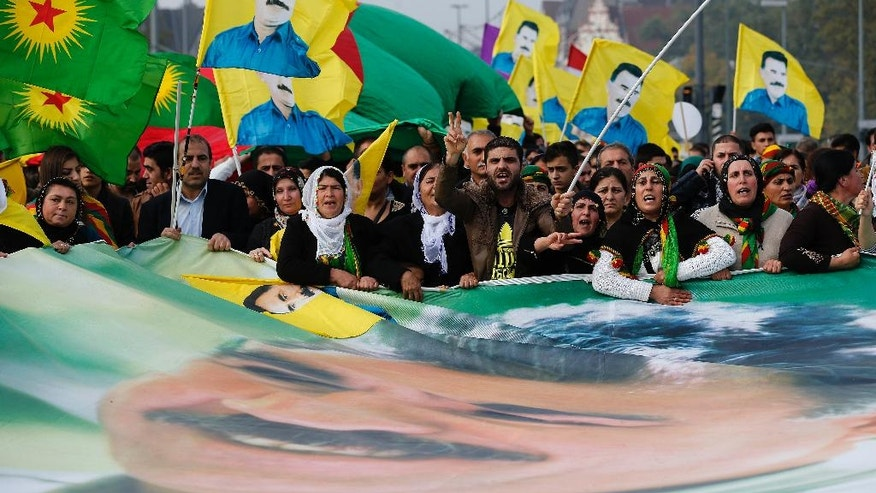 Some thousand Kurds protest against the Islamic State militants attack on the Syrian city Kobani with a flag showing Kurdistan Workers' Party imprisoned leader Abdullah Ocalan in Duesseldorf, Germany, Saturday, Oct. 11, 2014.(AP Photo/Frank Augstein)
