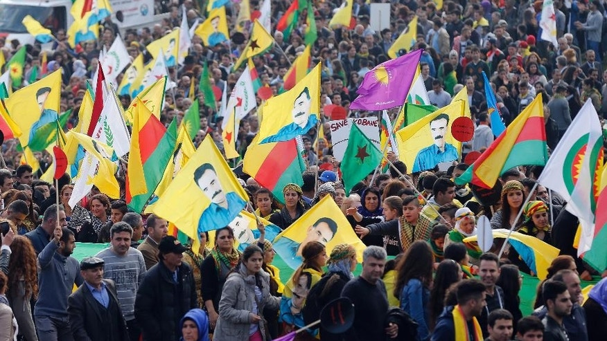 Some thousand Kurds with flags depicting Kurdistan Workers' Party imprisoned leader Abdullah Ocalan protest against the Islamic State militants attack on the Syrian city Kobani in Duesseldorf, Germany, Saturday, Oct. 11, 2014. (AP Photo/Frank Augstein)