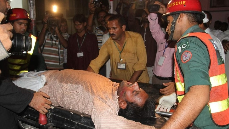 Pakistani rescue workers rush an injured person to a local hospital in Multan, Pakistan, Friday, Oct. 10, 2014.  A stampede at a political rally of Pakistan's former cricketer turned politician, Imran Khan, left some scores of people dead and dozens more injured, police said. (AP Photo/Asim Tanveer)
