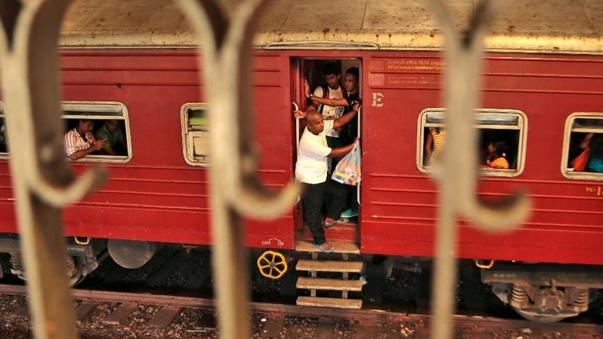"People ride a train that is about to reach Fort railway station in Colombo, Sri Lanka, Saturday, Oct. 11, 2014. The ""Queen of Jaffna,"" a once-popular train linking the ethnic Tamil's northern heartland to the rest of Sri Lanka before a bloody civil war cut the link 24 years ago, chugs back into service next week, reinforcing the government's authority in a region once controlled by Tamil rebels. President Mahinda Rajapaksa will inaugurate service along the 400-kilometer (250-mile) route between Jaffna and Colombo, the capital, in a ceremony Monday. (AP Photo/Eranga Jayawardena)"