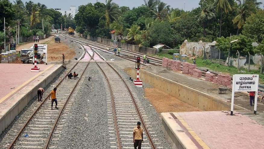 "Workers labor on train tracks leading to Jaffna station in Jaffna, Sri Lanka, Saturday, Oct. 11, 2014. The ""Queen of Jaffna,"" a once-popular train linking the ethnic Tamil's northern heartland to the rest of Sri Lanka before a bloody civil war cut the link 24 years ago, chugs back into service next week, reinforcing the government's authority in a region once controlled by Tamil rebels. President Mahinda Rajapaksa will inaugurate service along the 400-kilometer (250-mile) route between Jaffna and Colombo, the capital, in a ceremony Monday. (AP Photo/Maryathas Newtan)"