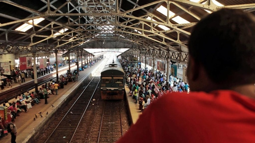 "A Sri Lankan man watches a train as commuters wait to board at Fort railway station in Colombo, Sri Lanka, Saturday, Oct. 11, 2014. The ""Queen of Jaffna,"" a once-popular train linking the ethnic Tamil's northern heartland to the rest of Sri Lanka before a bloody civil war cut the link 24 years ago, chugs back into service next week, reinforcing the government's authority in a region once controlled by Tamil rebels. President Mahinda Rajapaksa will inaugurate service along the 400-kilometer (250-mile) route between Jaffna and Colombo, the capital, in a ceremony Monday. (AP Photo/Eranga Jayawardena)"