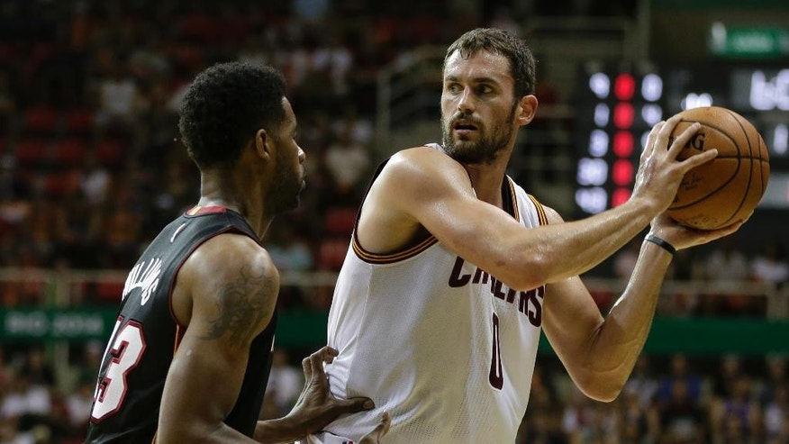Cleveland Cavaliers' Kevin Love, right, moves the ball under pressure from Miami Heat's Shawne Williams during a NBA preseason basketball game that's part of the NBA Global Games in Rio de Janeiro, Brazil, Saturday, Oct. 11, 2014. (AP Photo/Felipe Dana)